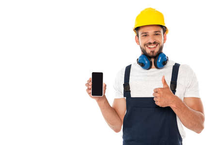 Photo pour Smiling handyman in workwear showing like gesture while holding smartphone with blank screen isolated on white - image libre de droit