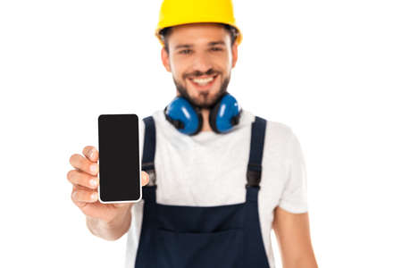 Photo pour Selective focus of smiling workman showing smartphone with blank screen isolated on white - image libre de droit