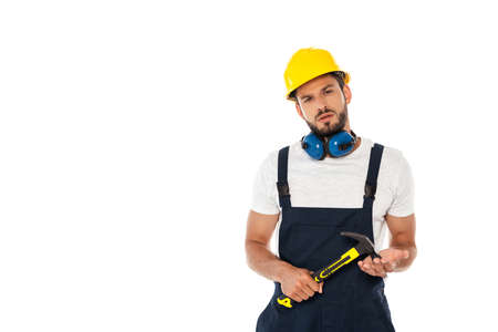 Photo pour Handsome workman in uniform and hardhat holding hammer and looking at camera isolated on white - image libre de droit