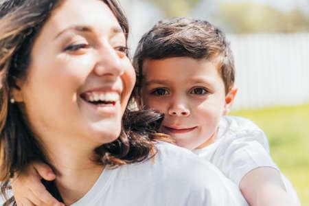 Photo pour selective focus of cheerful boy smiling near happy mother - image libre de droit
