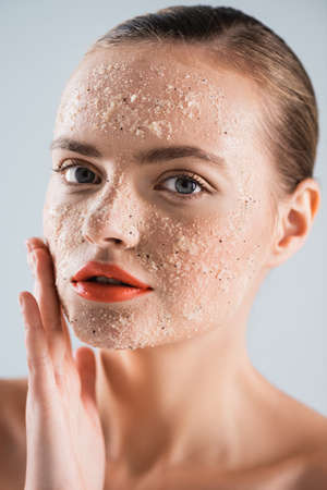 Photo pour close up of naked young woman applying scrub isolated on white - image libre de droit