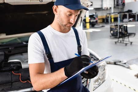 Photo pour Auto mechanic writing on clipboard near open hood of car at service station - image libre de droit