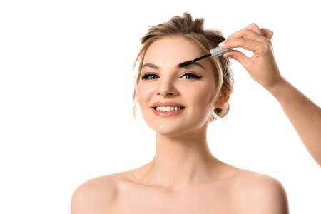 Photo pour hand with brow mascara near smiling naked beautiful blonde woman isolated on white - image libre de droit