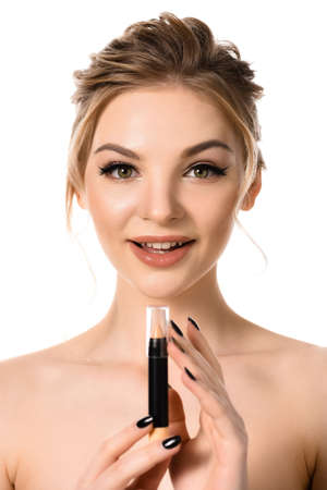 Photo for naked beautiful blonde woman with makeup and black nails looking at stick concealer isolated on white - Royalty Free Image