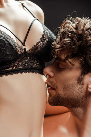 Photo pour Shirtless man kissing belly of woman in lace bra isolated on black - image libre de droit