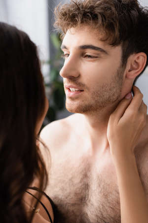 Photo for selective focus of shirtless man looking at brunette woman - Royalty Free Image