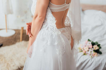Photo for Cropped view of bride in underwear and veil putting on lace wedding dress in bedroom - Royalty Free Image