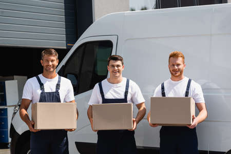 Photo for Movers in uniform looking at camera and holding cardboard boxes near truck on urban street - Royalty Free Image