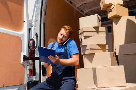 Photo for Loader in uniform holding clipboard while talking on smartphone near packages in truck - Royalty Free Image