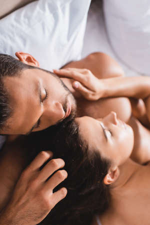 Photo pour Overhead view of shirtless man touching hair of young woman on bed - image libre de droit