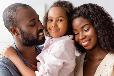 Photo pour african american man holding daughter on hands near mother at home - image libre de droit