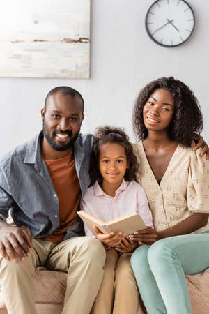 Photo pour young african american parents and child with book looking at camera while sitting at home - image libre de droit