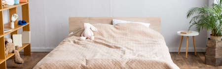Foto de horizontal image of bedroom, bed with beige blanket, rack with books and potted plant - Imagen libre de derechos