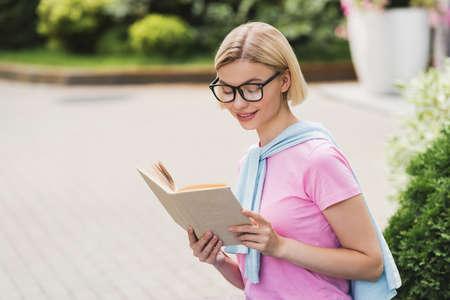 Photo pour young blonde student in glasses reading book outside - image libre de droit