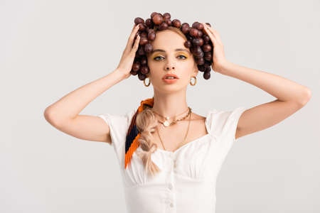 Photo pour rustic blonde woman posing with grapes on head isolated on white - image libre de droit