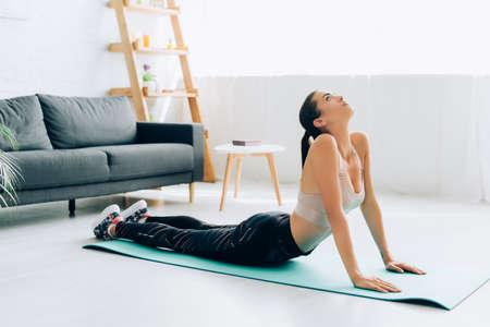 Photo pour Selective focus of fit sportswoman stretching back on fitness mat at home - image libre de droit