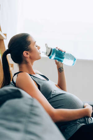 Photo pour Selective focus of pregnant sportswoman drinking water while sitting on sofa at home - image libre de droit