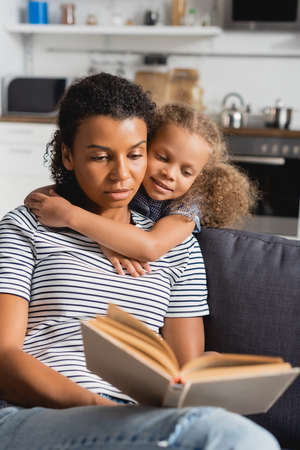 Photo pour selective focus of african american girl embracing nanny in striped t-shirt reading book on couch - image libre de droit