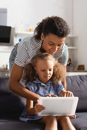 Photo pour young african american babysitter using digital tablet together with girl sitting on sofa - image libre de droit