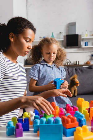 Photo pour selective focus of african american nanny in striped t-shirt and girl in dress playing with colorful building blocks at home - image libre de droit