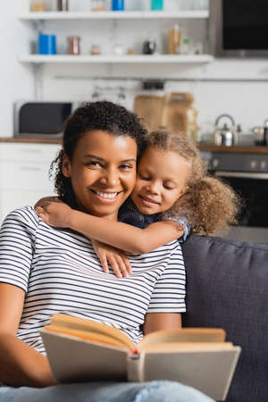 Photo pour selective focus of african american nanny holding book and looking at camera while child embracing her neck - image libre de droit