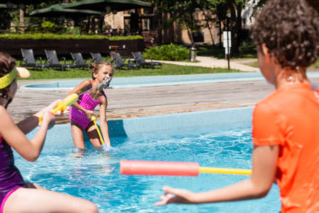Photo for selective focus of boy and girls fighting with water guns while having fun near pool - Royalty Free Image