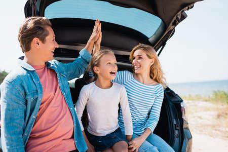 Photo pour Selective focus of parents giving high five near daughter and car on beach - image libre de droit