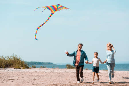 Photo pour Family with daughter and kite running on beach during vacation - image libre de droit