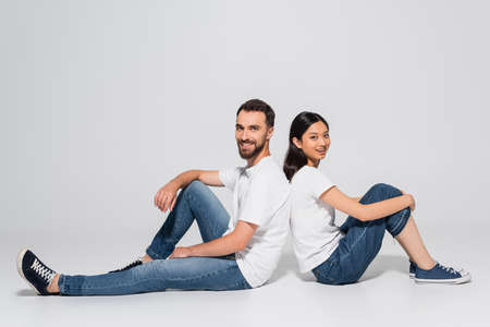 Photo pour young asian woman and bearded man in white t-shirts and jeans sitting on white and looking at camera - image libre de droit