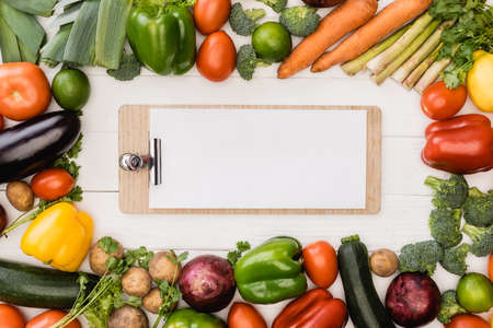 Photo for top view of fresh ripe vegetables and fruits near empty clipboard on wooden white background - Royalty Free Image