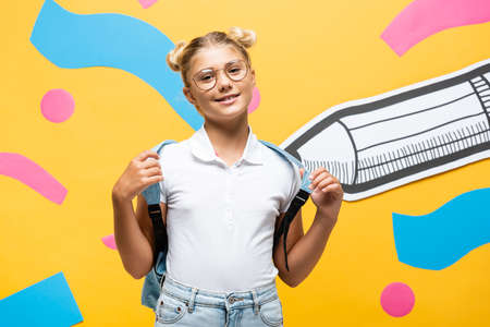 Photo pour pleased schoolgirl in eyeglasses looking at camera near paper cut pencil and multicolored elements on yellow - image libre de droit