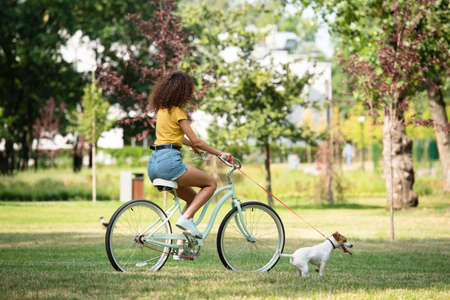 Photo for Selective focus of young woman holding jack russell terrier on leash while cycling in park - Royalty Free Image