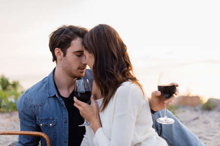 Photo for Young couple with glasses of wine kissing on beach at sunset - Royalty Free Image