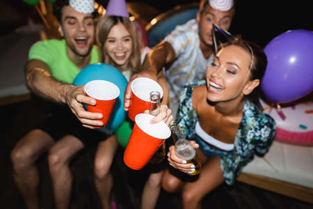 Photo for Selective focus of young friends in party caps clinking with beer and disposable cups at night - Royalty Free Image
