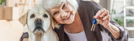 panoramic shot of smiling senior woman embracing dog and holding keys, moving concept
