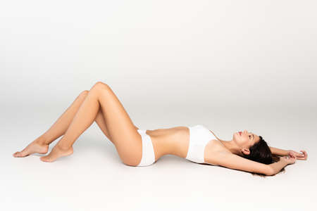 Photo pour Sexy woman in white underwear looking away, while lying on gray - image libre de droit