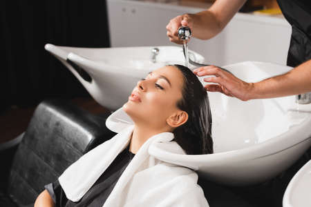 Photo pour hairstylist washing hair of young woman in barbershop - image libre de droit