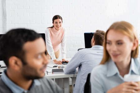 Foto de Smiling businesswoman looking at colleague near devices in office - Imagen libre de derechos