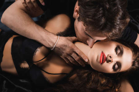 Photo pour Top view of man kissing neck of woman with red lips in lingerie - image libre de droit