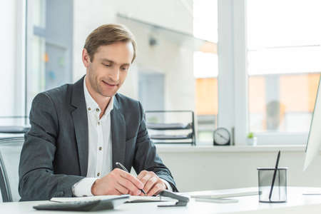 Photo for Smiling businessman writing in notebook, while sitting at table with blurred window on background - Royalty Free Image