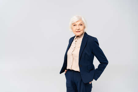 Photo pour Senior woman looking at camera while standing with hands in pockets of pants isolated on gray - image libre de droit