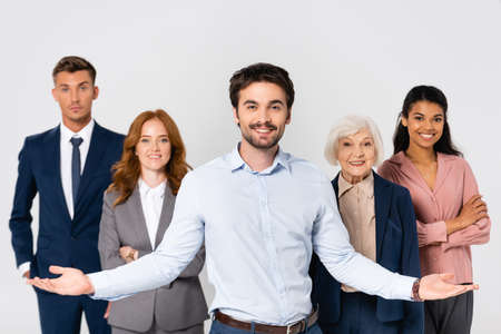 Photo pour Cheerful businessman pointing with hands near multiethnic colleagues isolated on gray - image libre de droit