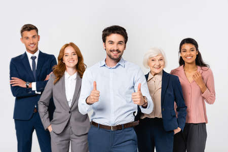 Photo pour Smiling businessman showing thumbs up near cheerful multiethnic colleagues isolated on gray - image libre de droit