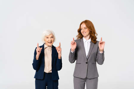 Photo pour Smiling businesswomen pointing with fingers isolated on gray - image libre de droit