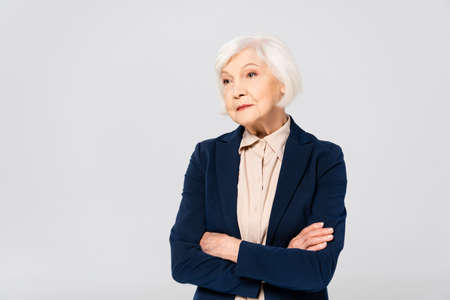 Photo pour Senior woman in jacket standing with crossed arms isolated on gray - image libre de droit