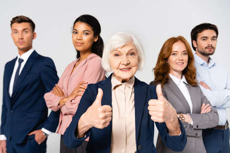 Foto de Smiling businesswoman showing like near multicultural businesspeople on blurred background isolated on gray - Imagen libre de derechos