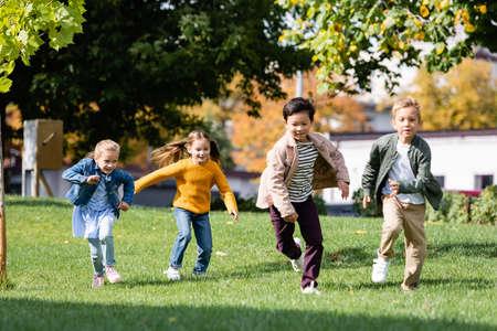 Photo pour Smiling multiethnic children running on grass in park - image libre de droit
