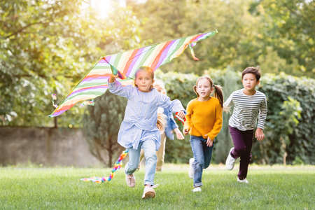 Photo for Girl holding flying kite while running near multiethnic friends in park - Royalty Free Image