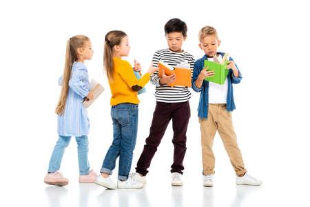 Foto de Multiethnic kids holding colorful books on white background - Imagen libre de derechos