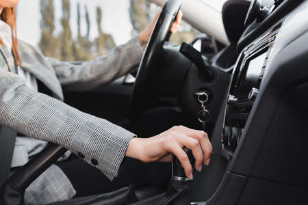 Photo pour cropped view of businesswoman shifting gear lever while driving car on blurred background - image libre de droit